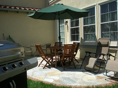 Backyard with gas Barbeque grill, patio furniture & small garden.