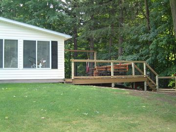 View of west side of cottage and back deck and steps down to dock.