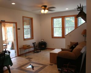 Eastbrook house photo - Living room with gas heat-stove, open to screen porch/deck. Views to lake.