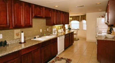 Granite countertops. Cherry cabinets. Notice breakfast nook in rear.