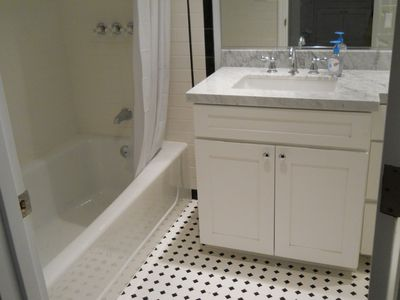 "Large 66"" extra deep soaking tub, Cararra marble slab countertop, deco tiles."