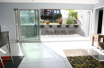 Glass doors slide to open the living room up to a private patio with bar stools