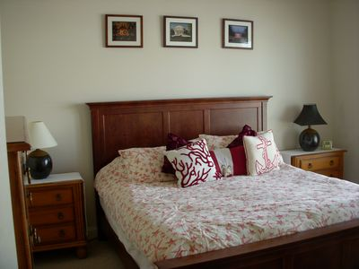 master bedroom with king bed, flat screen TV, an ceiling fan with remote control