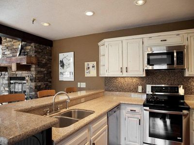 Fully equipped kitchen features granite counters, wine cooler