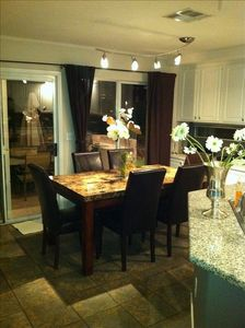 Dining room with marble table, custom stone floor throughout.