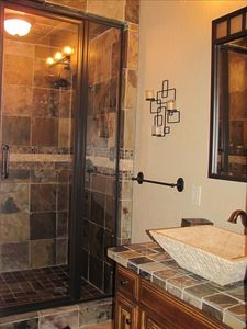 This upstairs bath features custom tile, steam shower and an imported stone sink