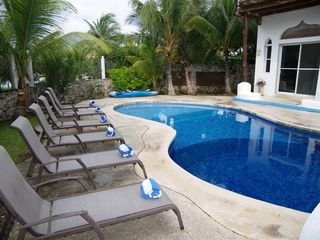 Akumal villa photo - pool deck with 10 beach tanning beds. bedroom entry in background.