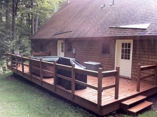 The back deck with hot tub, BBQ grills and doors to the left and right units