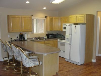 Kitchen with plush swiveling bar stools and cooking supplies provided