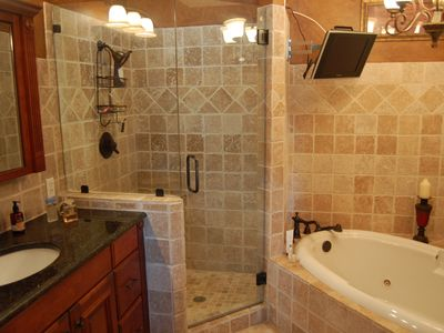 Master Bath with whirlpool, shower and Granite Counter. TV over tub
