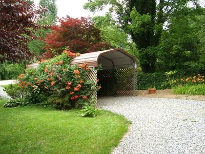 A carport is located at the other end of the circular driveway.