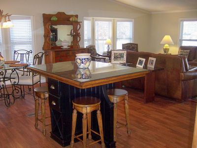 Large open living area with kitchen, island, dinette, and living room; all with expansive views of the lake.