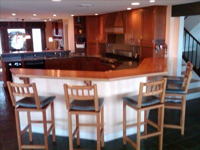 Plum Island house rental - Gourmet kitchen with seating for five at counter. Kitchen table for 9 is beyond