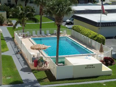 Cocoa Beach condo rental - Heated pool with plenty of chairs, tables, umbrellas and chaises.