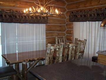 Custom built 8 ft. log table and cushion log chairs and benches.