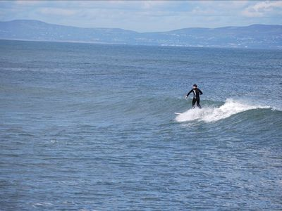 Surfing off Castlerock beach with Greencastle and Donegal hills in the distance.