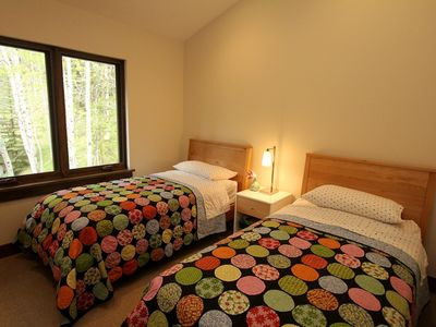 Bedroom #5 features two twin beds and a view to the aspen glade