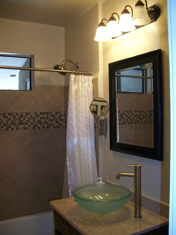 New bathroom with granite, glass vessel sink, ceramic and glass tile surround