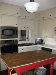 Kitchen blending antique and modern, with stainless appliances, gas cooktop.