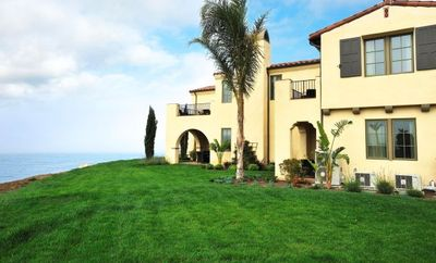 Backside view with lush open areas and stunning views of the Pacific Ocean.