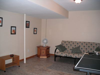 Lower level game room with futon, ping-pong table and Game Cube.