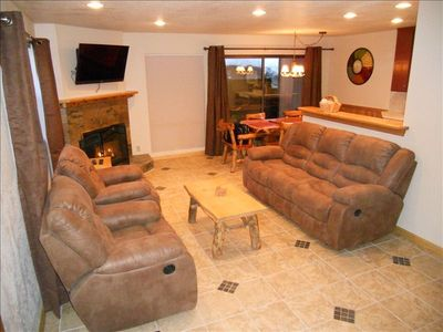 Living Room with gas fireplace, relaxing reclining coach and chairs, HDTV.