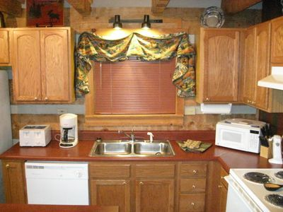 Beautiful oak cabinets and a window with a gorgeous secluded wooded view
