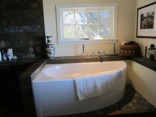 Japanese soaking tub, raised for view of ocean and cliff, shower left. Private.