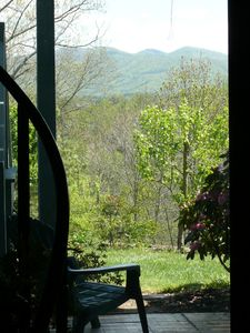 View from glass doors of the mountains and fruit trees.