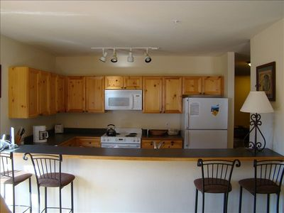 Kitchen, with range, fridge, microwave and free high speed internet at the bar.