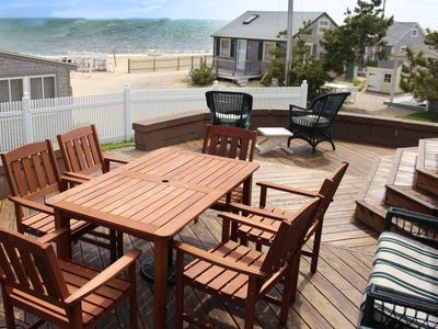 Private deck with ample seating and large fenced grass yard, steps from the sand