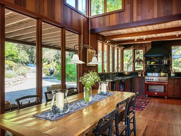 """Carmel Valley house rental - Welcome to """"Les Restanques""""! Front door opens on to a French farm table surrounded by Hitchcock chairs; Italian lamp hung from the 20 foot cathedral ceiling lights the dining table; gourmet kitchen is just beyond."""