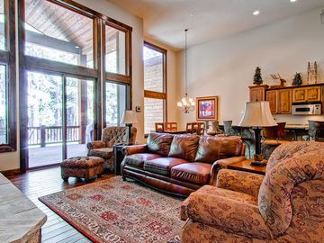 """Baldy Mountain Breckenridge townhome rental - The stylish great room features a rock fireplace, comfortable seating, a 47"""" flatscreen TV, and views of the surrounding forest."""