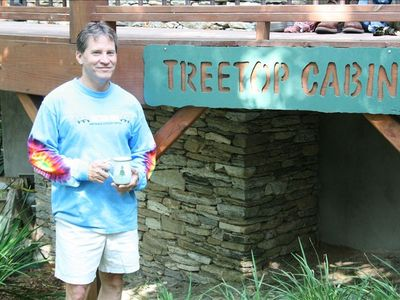 Owner Jim with coffee in front of deck and TreeTop sign