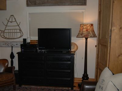 storage space in drawers and cabinet along with a flat screen TV