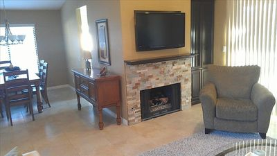 "Living room gas fireplace with 42"" HD TV and dining room in the background"