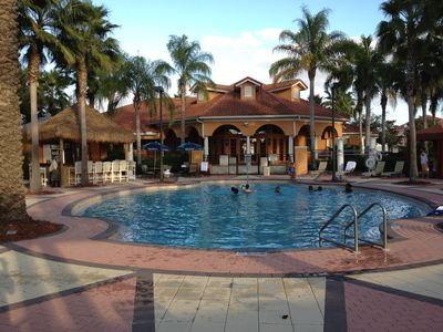 large club house heated pool, with back view of the Club house and the Tiki Bar
