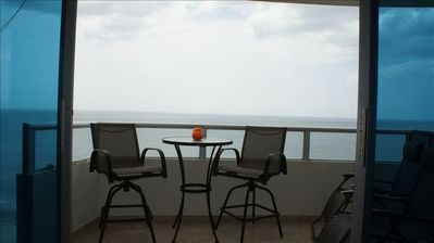 Balcony with a BBQ grill. Spectacular view of the ocean, beach and mountains.