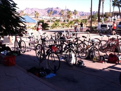 All the bikes at the front entrance and parking lot with a view of the mountains