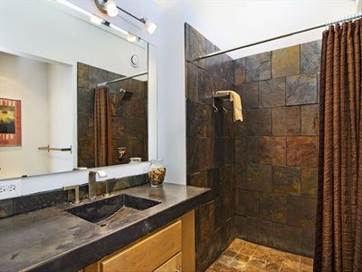 Both master baths featurecustom concrete sinks and slate showers.