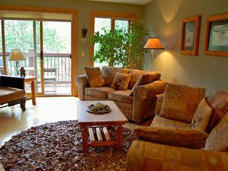 Canmore condo photo - Cozy living room w/ leather shag rug, log furniture, and single sleeper sofas