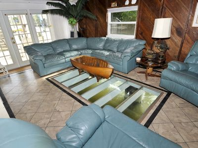 Living room with glass floor over the water.