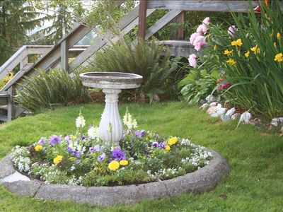 The bird bath in the front yard is surrounded by pretty flowers.