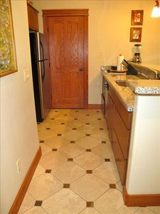 Tiled kitchen with full-size fridge, microwave, stove top and dishwasher.