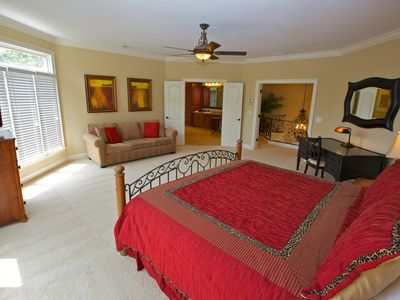 Spacious master bedroom w/ king-size bed, queen-size sofa-bed, and private desk.