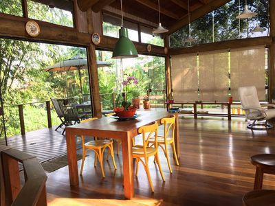 Wide beach house with wooden structure and embraced by the tree canopy