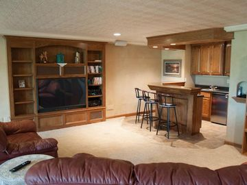 The basement home theatre, wet bar, and game area will bring the group together!