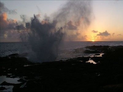Hawaii Sunset from backyard with waves crashing against lava rocks.
