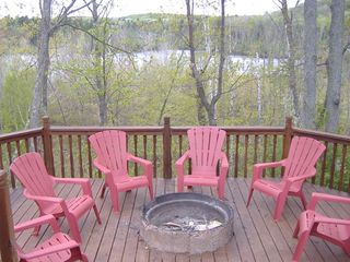 Birchwood cabin photo - Enjoy sunsets and fires with the peaceful lake behind the house (chairs are red)