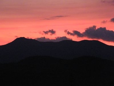 Rosy red glow of sunset over the mountains - view from deck.